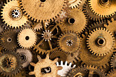 Aged gears cogwheels background. Retro mechanical clock accessories close-up. Shallow depth field, soft focus.