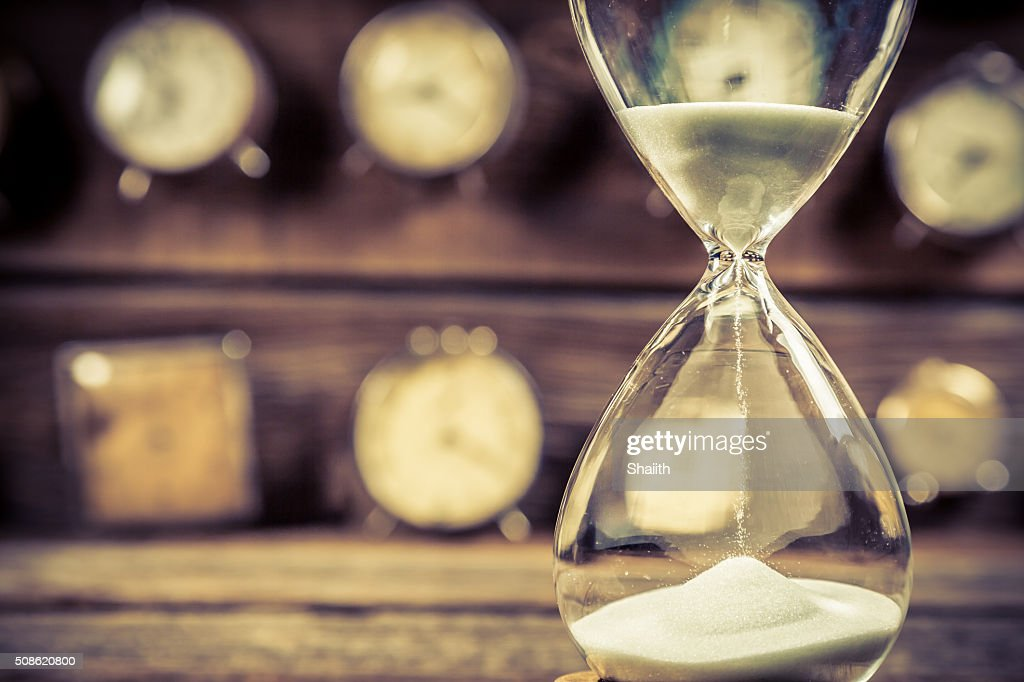 Aged hourglass with flowing sand : Stock Photo