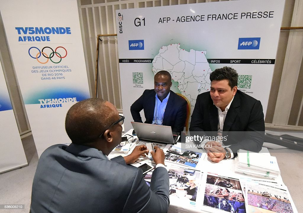 Agence France Presse's (AFP) commericial director for Africa Joaquin Iturralde(R) and his colleague Jeau-Paul Ahoussi speak with a visitor to the AFP stand during the DISCOP conference in Abidjan on May 31, 2016. / AFP / SIA