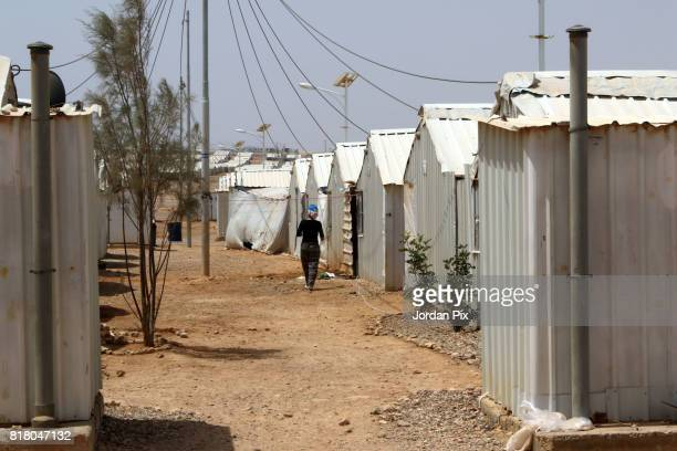 UN agency staff walks between Syrian refugees makeshift homes at the Azraq camp for Syrian refugees the newest camp in Jordan that hosts 54000...