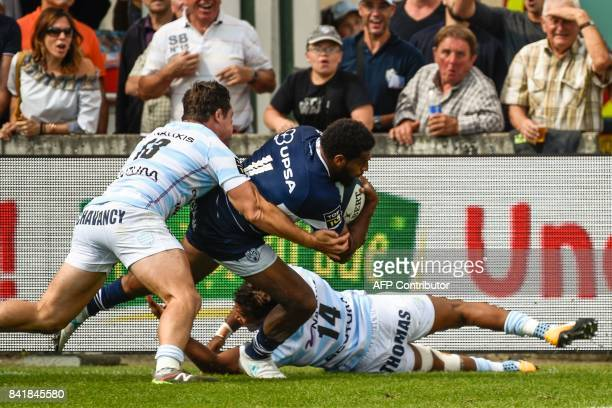 Agen's New Zealander wing George Tilsley scores a try despite Racing's Henri Chavancy during the French Top 14 rugby union match between Agen and...