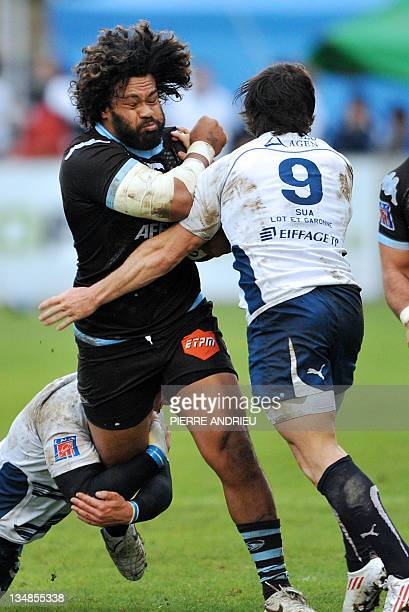 Agen's scrumhalf Maxime Machenaud collapses with Bayonne' number 8 Sione Lauaki during the French Top 14 rugby union match Agen vs Bayonne on...