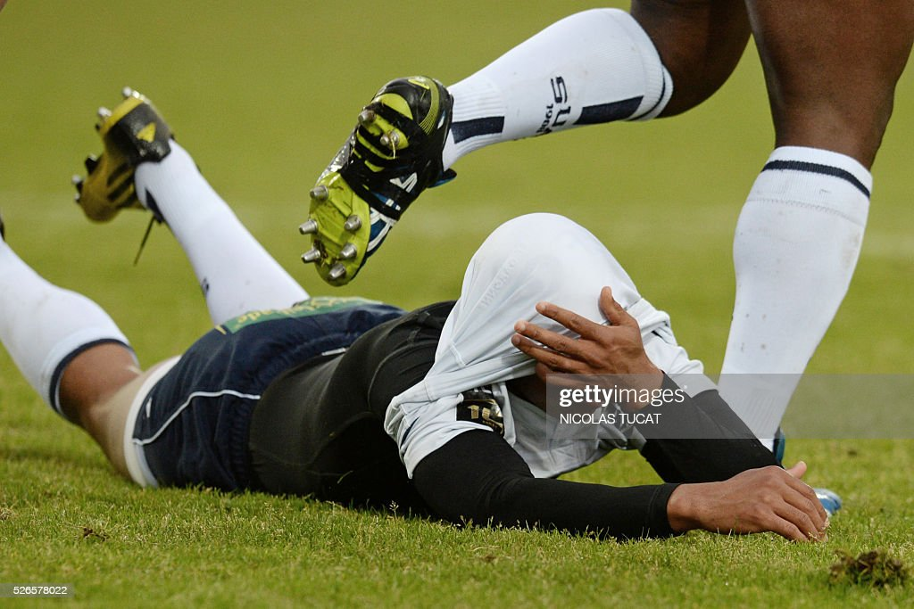 Agen's South African flyhalf Burton Francis (R) lays on the ground masked by his own shirt during the French Top 14 rugby union match between Agen and Brive on April 30, 2016 at the Armandie stadium in Agen, southwestern France.