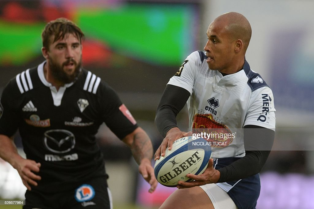 Agen's South African flyhalf Burton Francis (R) runs with the ball during the French Top 14 rugby union match between Agen and Brive on April 30, 2016 at the Armandie stadium in Agen, southwestern France.
