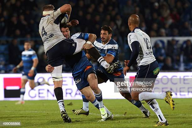 Agen's South African lock Marco Kotze is tackled by Castre's French centre Thomas Combezou during the French Top 14 rugby union match between Agen...