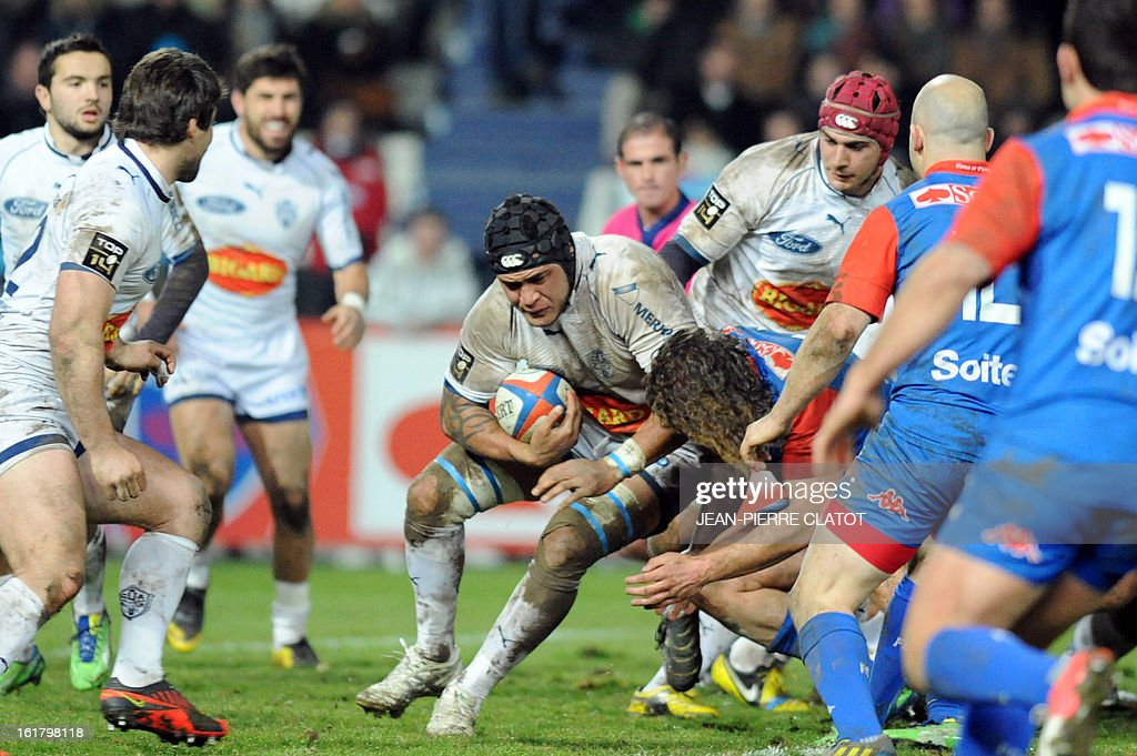 Agen's Tongan centre Ueleni Fono (C) tries to get through a tackle during the French Top 14 rugby union match Grenoble (FCG) vs Agen (SU) on February 16, 2013 at the Stade Lesdiguieres in Grenoble. AFP PHOTO / Jean Pierre Clatot