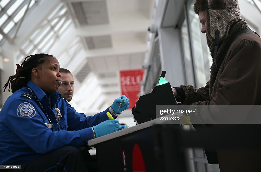A TSA agent checks a traveler's identification at a special TSA Pre-check lane at Terminal C of the LaGuardia Airport on January 27, 2014 in New York City. Once approved for the program, travelers can use special expidited Precheck security lanes. They can also leave on their shoes, light outerwear and belt, as well as keep their laptop and small containers of liquids inside carry-on luggage during security screening. The TSA plans to open more than 300 application centers across the country.