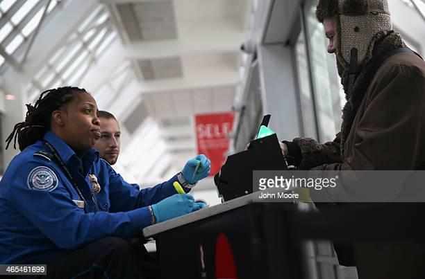TSA agent checks a traveler's identification at a special TSA Precheck lane at Terminal C of the LaGuardia Airport on January 27 2014 in New York...