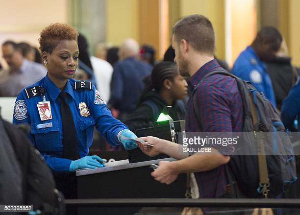 Agent checks the ID's of passengers as they pass through a security checkpoint on the way to their flights at Reagan National Airport in Arlington...