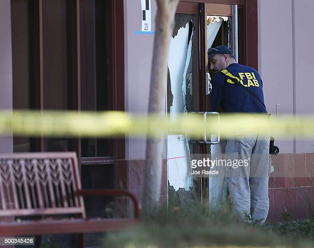 A FBI agent is seen next to a broken out glass door on the building at the Inland Regional Center were 14 people were killed on December 7 2015 in...