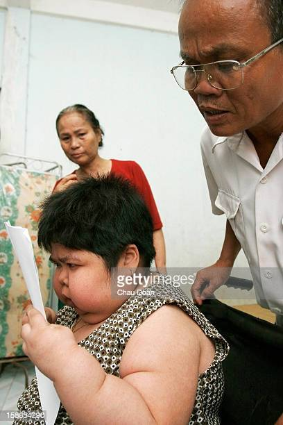 Agent Orange victim Nguyen Thi Nam Ha tries to read while her mother Tran Thi Huyen and her father Nguyen Tho Tue watch on at their house in Vung Tau...