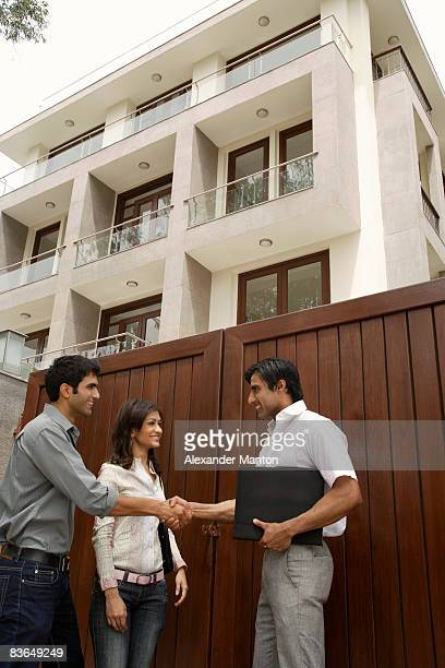 Agent shaking hands with young couple