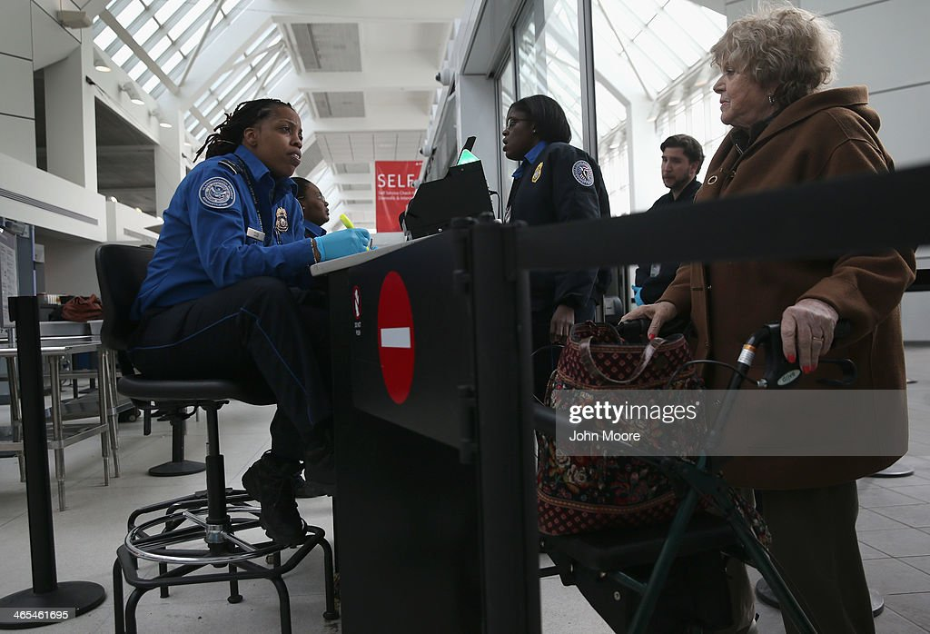 A TSA agent speaks with a traveler at a special TSA Pre-check lane at Terminal C of the LaGuardia Airport on January 27, 2014 in New York City. Once approved for the program, travelers can use special expidited Pre-check security lanes. They can also leave on their shoes, light outerwear and belt, as well as keep their laptop and small containers of liquids inside carry-on luggage during security screening. The TSA plans to open more than 300 application centers across the country.