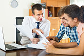 Male agent consulting young couple about offer details in office