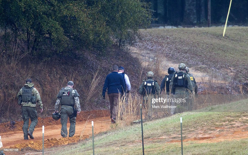 FBI agents and Alabama State Troopers walk up the hill to the bunker to process the crime scene February 5, 2013 in Midland City, Alabama. The suspect, Jimmy Lee Dykes was killed when the FBI stormed the bunker and rescued the 5 year-old child named Ethan after 6 days of captivity.
