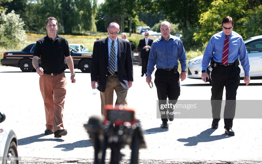 FBI agents and police officials walk to the microphones to give the news media an update on their search of a field for the possible remains of former Teamsters' union president Jimmy Hoffa June 17, 2013 in Oakland Township, Michigan. The agents were acting on a tip provided by Tony Zerilli, 85, a former mobster, who was released from prison in 2008. Hoffa, who had reported ties to organized crime, went missing in July of 1975.