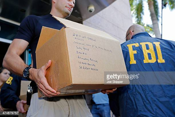FBI agents carry boxes from the headquarters of CONCACAF after it was raided on May 27 2015 in Miami Beach Florida The raid is part of an...
