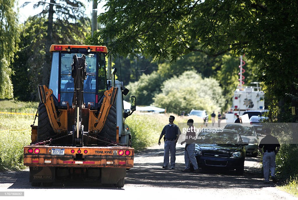 FBI agents direct a vehicle carrying digging machinery to a field to dig for the possible remains of former Teamsters union president Jimmy Hoffa June 17, 2013 in Oakland Township, Michigan. The agents were acting on a tip provided by Tony Zerilli, 85, a former mobster, who was released from prison in 2008. Hoffa, who had reported ties to organized crime, went missing in July of 1975.