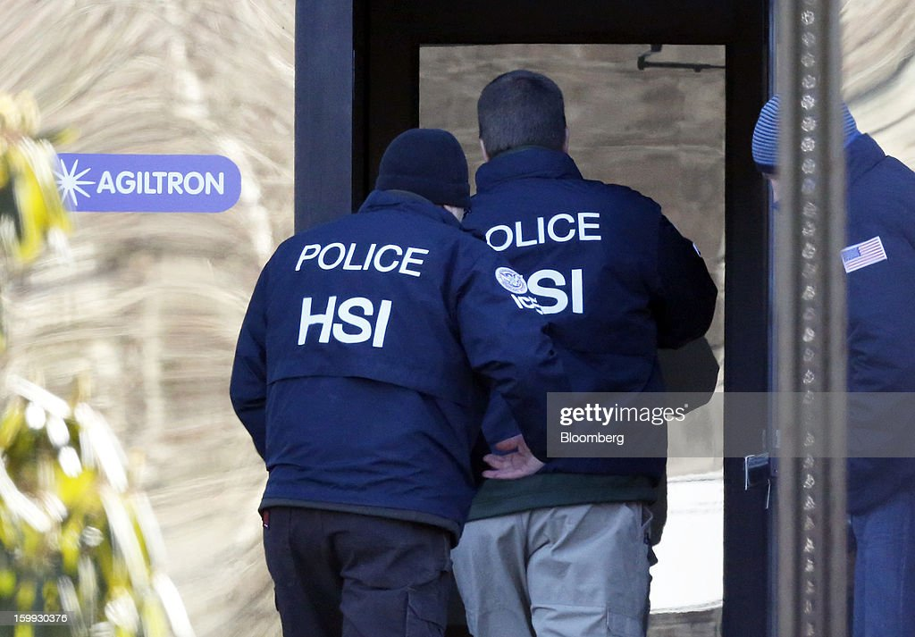 Agents from the U.S. Immigration and Customs Enforcement's Homeland Security Investigations (HSI) unit enter the offices of Agiltron in Woburn, Massachusetts, U.S., on Wednesday, Jan. 23, 2013. Agiltron describes itself as providing clients with 'optical communication and sensing solutions' on the company website. Photographer: Bizuayehu Tesfaye/Bloomberg via Getty Images