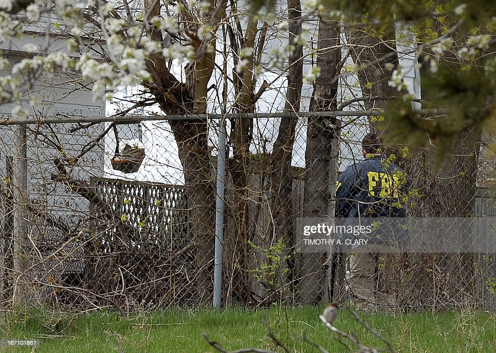 FBI agents investigate on April 20, 2013, the covered boat (rear) where Dzhokhar Tsarnaev was hiding and captured in Watertown, Massachusetts. Thousands of heavily armed police staged an intense manhunt April 29 for the Chechen teenager suspected in the Boston marathon bombings with his brother, who was killed in a shootout. Dzhokhar Tsarnaev, 19, defied the massive force after his 26-year-old brother Tamerlan was shot and suffered critical injuries from explosives believed to have been strapped to his body.