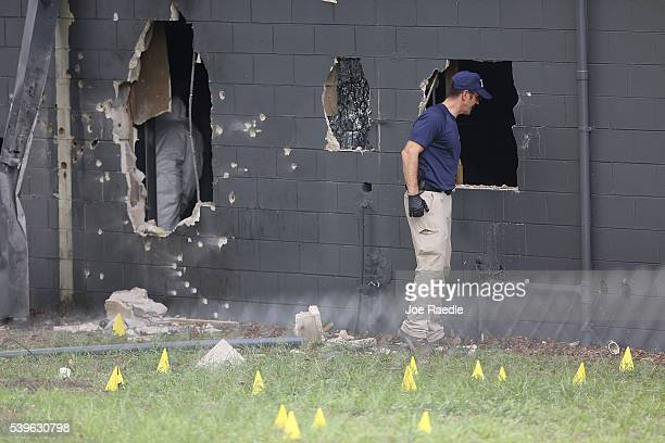 FBI agents investigate the damaged rear wall of the Pulse Nightclub where Omar Mateen allegedly killed at least 50 people on June 12 2016 in Orlando...