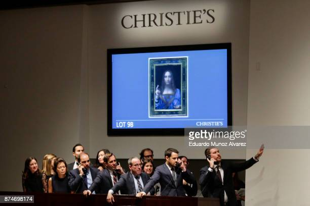 Agents speak on their phones with their clients while bidding on at the auction of Leonardo da Vinci's 'Salvator Mundi' during the PostWar and...