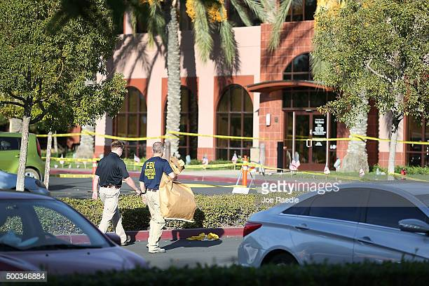 FBI agents walk through the parking lot as they investigate the scene in the building at the Inland Regional Center were 14 people were killed on...