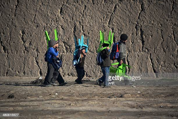 Aghan school children carry plastic chairs on their heads as they walk to school in the morning in MazariSharif on March 26 2014 The literacy rate in...