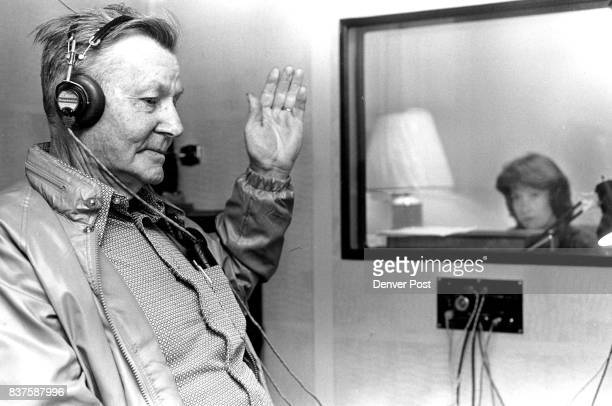 Aging Aged Denver Fay ***** of Denver raises his hand at the sound of the tone during a hearing test while Jane Nakata watches fro response to the...