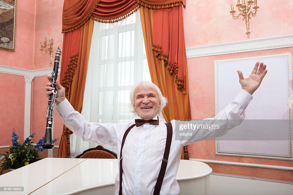 aging musician plays the clarinet : Stock Photo