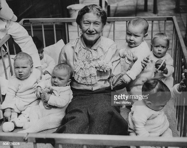 Agnes BadenPowell sister of Girl Guide leader Lady Olave BadenPowell pictured sitting in a play pen with a group of babies at Westminster Day Nursery...