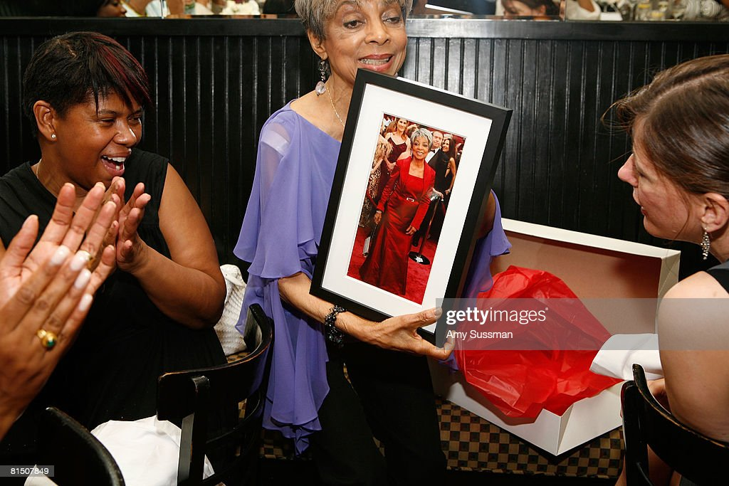 Agnes Cammock and Bridget Foley watch as Ruby Dee opens gifts at a celebration of Ruby Dee's style at Melba's restaurant on June 9, 2008 in New York City.