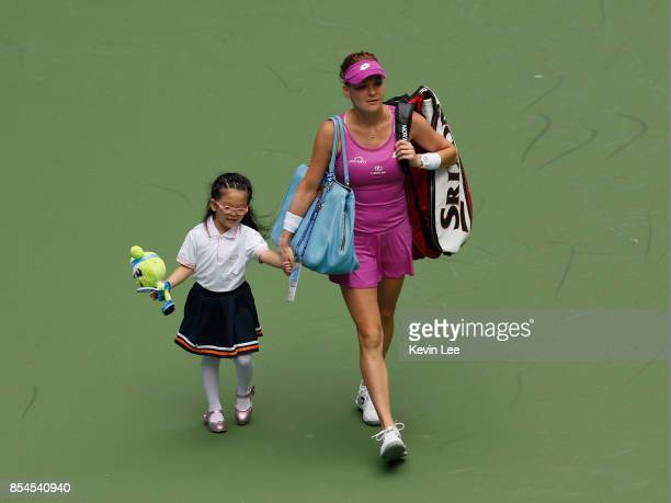 Agnieszka Radwanska of Poland enter the court with a little girl for the match against Ashleigh Barty of Australia in round 3 of Women's Single...