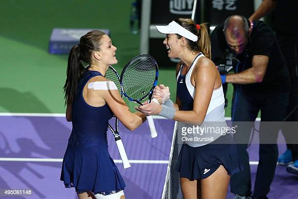 Agnieszka Radwanska of Poland shakes hands with Garbine Muguruza of Spain after defeating her in the semifinal match during BNP Paribas WTA Finals at...