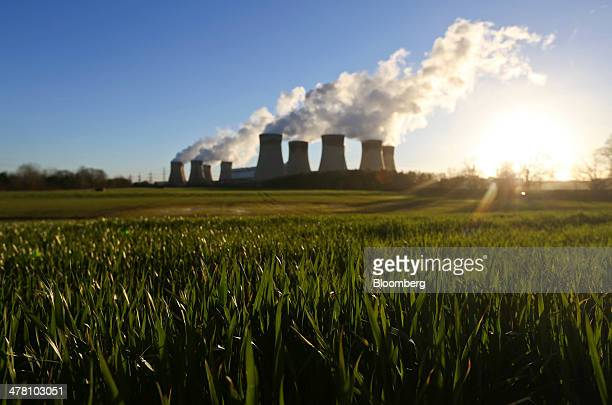Agricultural crops grow in a farmer's field as vapour rises from cooling towers at Drax Power Station operated by Drax Group Plc in Selby UK on...