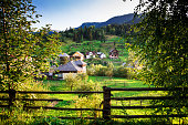 The beautiful agricultural landscape of rural Maramures in northern Romania. Through a clearing in the trees we can see some of the traditional houses of the village of Borsa. Horizontal color image w
