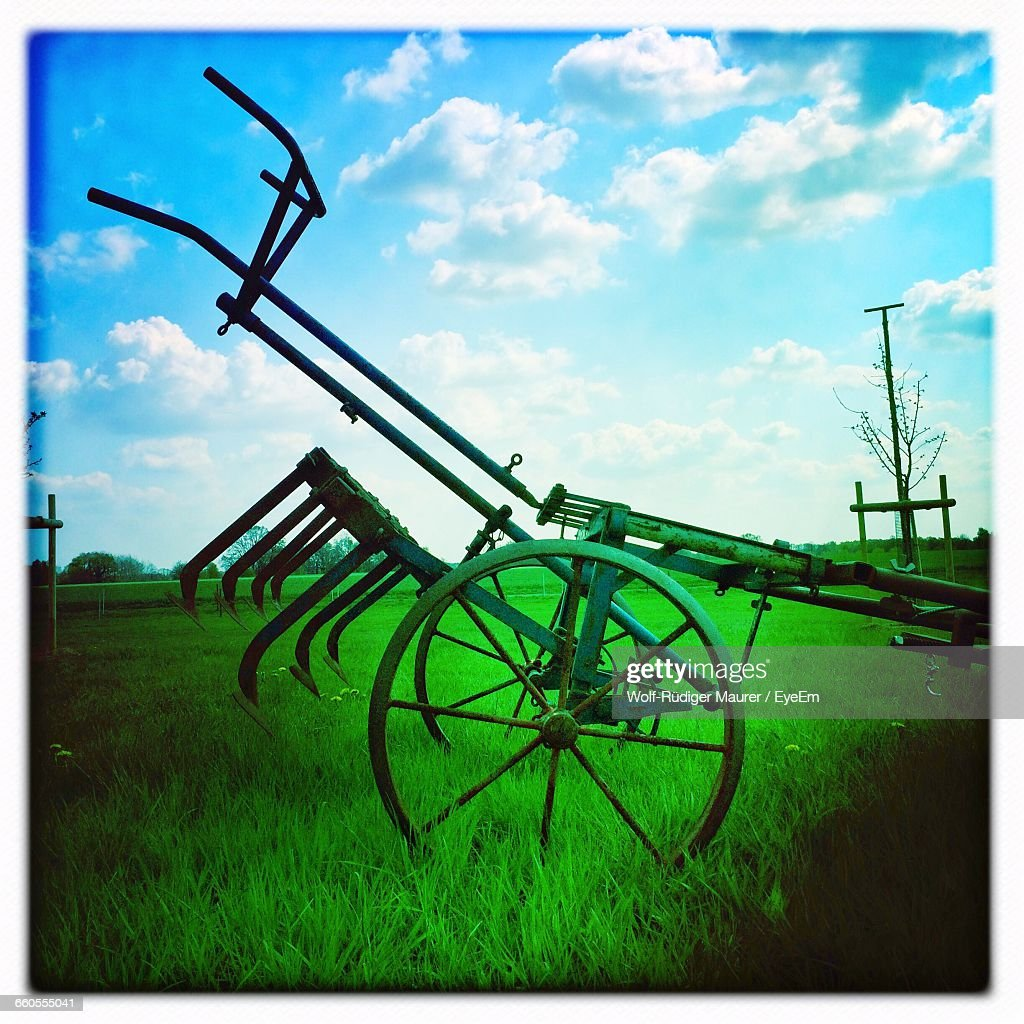 Agricultural Machinery On Grassy Field Against Sky