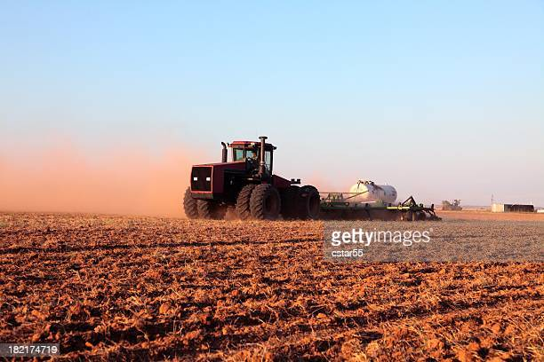 Agriculture: Farmer driving tractor with Fertilizer Tank in plowed field