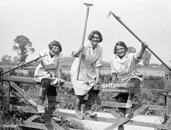 Agriculture In Britain During The First World War Members of the Women's Land Army smile as they hold their tools aloft while climbing over a gate on...