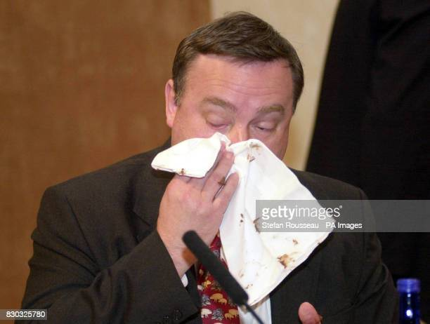 Agriculture Minister Nick Brown wipes his face after a woman threw a chocolate cake at the National Farmers Union Conference in London