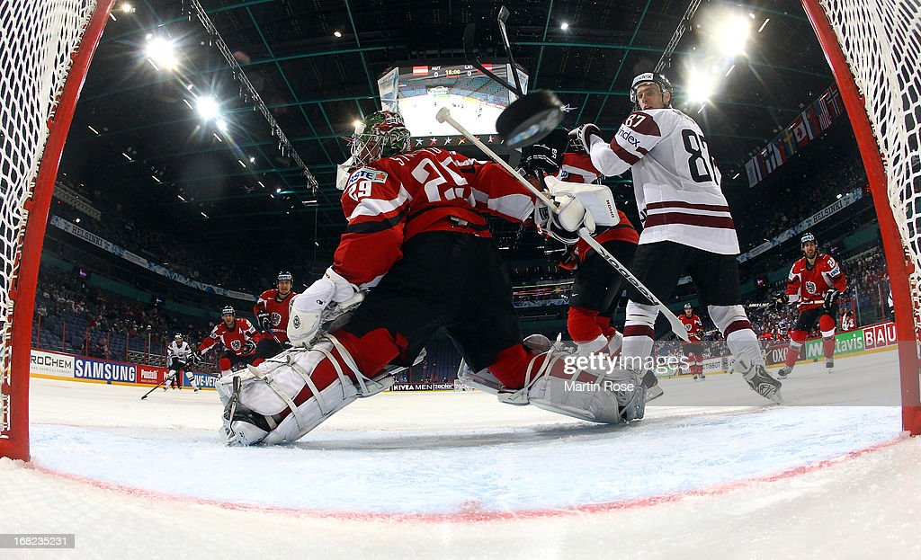 Agris Savlies (not pictured) of Latvia scores his team's 2nd goal over Bernhard Starkbaum (C), goaltender of Austria during the IIHF World Championship group H match between Austria and Latvia at Hartwall Areena on May 7, 2013 in Helsinki, Finland.
