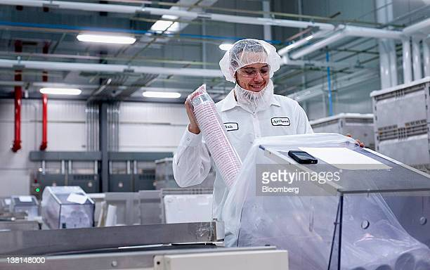 AgroFarma Inc employee Christian Murray loads Chobani Inc yogurt containers into a sleeving machine to be shrink wrapped at a facility in New Berlin...