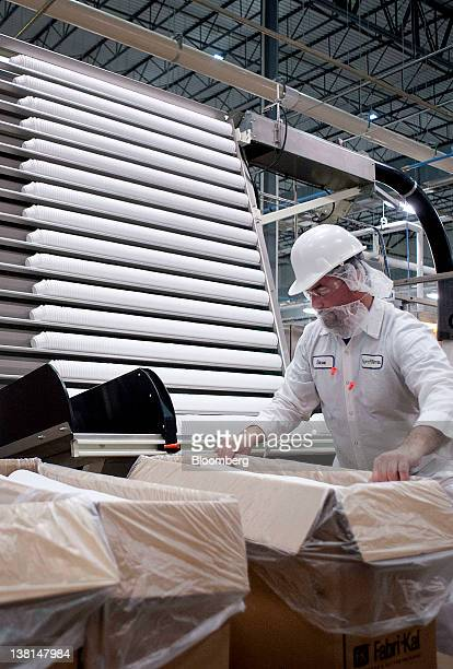 AgroFarma Inc employee Steve Plows loads Chobani Inc yogurt containers into a sleeving machine to be shrink wrapped at a facility in New Berlin New...