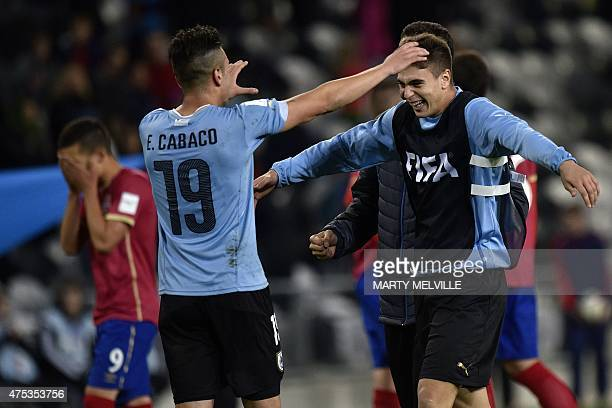 Agustin Ale of Uruguay celebrates their win with teammate Erick Cabaco as Stanisa Mandic of Serbia walks from the field dejected at the end of the...