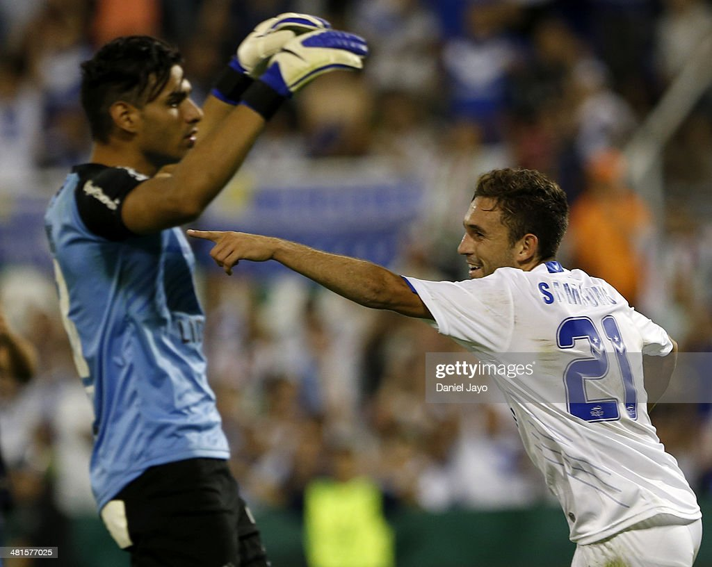 Agustin Allione (R) of Velez Sarsfield celebrates after scoring the fourth goal as Fernando Monetti of Gimnasia y Esgrima La Plata reacts during a match between Velez Sarsfield and Gimnasia y Esgrima La Plata as part of 10th round of Torneo Final 2014 at Jose Amalfitani Stadium on March 29, 2014 in Buenos Aires, Argentina.