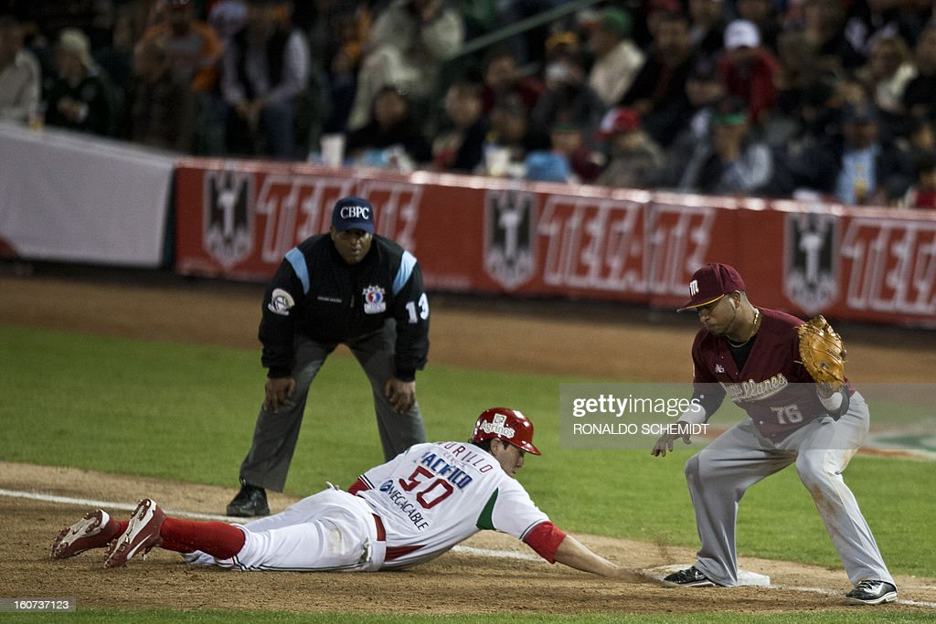 Agustin Murillo (bottom) of Yaquis de Obregon of Mexico slides safe at first base against Magallanes of Venezuela during the 2013 Caribbean baseball series on February 4, 2013, in Hermosillo, Sonora State, northern Mexico. AFP PHOTO/Ronaldo Schemidt