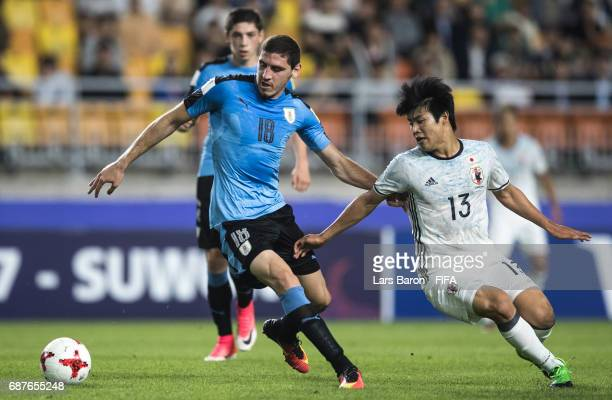 Agustin Rogel of Uruguay is challenged by Yuto Iwasaki of Japan during the FIFA U20 World Cup Korea Republic 2017 group D match between Uruguay and...