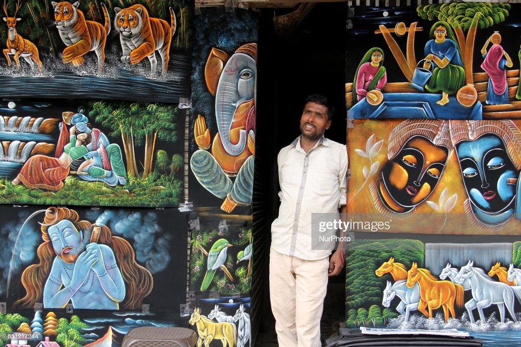 Ahead of the Independence Day, paintings were displayed in Delhi's busiest market, as one of the sellers awaits customers on the hot and humid day in Delhi, India, on 14 August 2017.