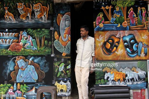 Ahead of the Independence Day paintings were displayed in Delhi's busiest market as one of the sellers awaits customers on the hot and humid day in...