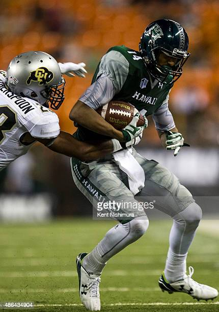 Ahkello Witherspoon of the Colorado Buffaloes stops Marcus Kemp of the Hawaii Warriors during the second half of a college football game at Aloha...
